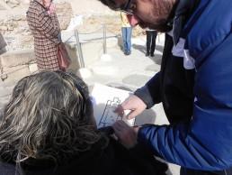 Visita a la Illeta por un colectivo de discapacitados visuales - tocando una guía braille con relieves del yacimiento